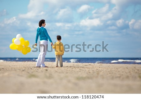 Mother and little son with yellow balloons on the beach on beautiful summer day