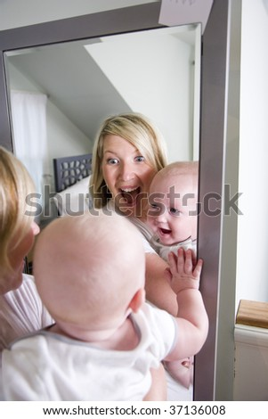Mother and 7 month old baby playing in mirror