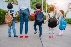 Mother and pupil and kids holding hands going to school in first class with schoolbag or satchel walking to school bus, Parent and son,sister preschool