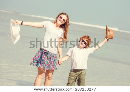 Mother and red haired son having family time on holidays walking along the beach. Travel, holiday, vacation concept