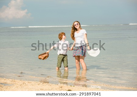 Mother and red haired son having family time on holidays waving with hats on  the beach. Travel, holiday, vacation concept