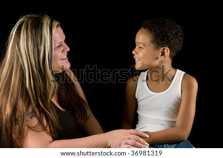 Mother and seven-year old son enjoy a laugh; working-class single mom (with tattoos) and mixed-race child in tender relationship.