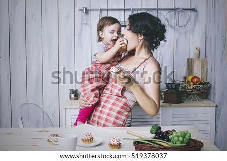 Mother and small child in the kitchen at home beautiful and happy aprons