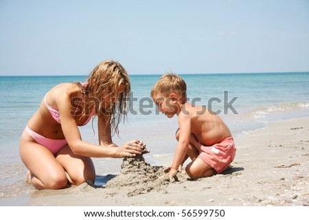mother and son building sand castle on beach