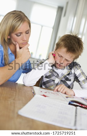 Mother and son concentrating on homework together