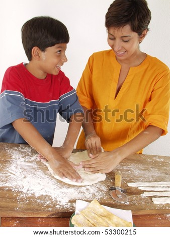 Mother and son cooking pizza.