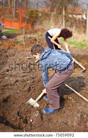 Mother and son digging into the garden for planting trees