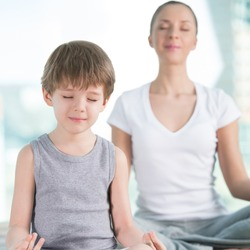 Mother and son doing yoga exercise at home - focus on son