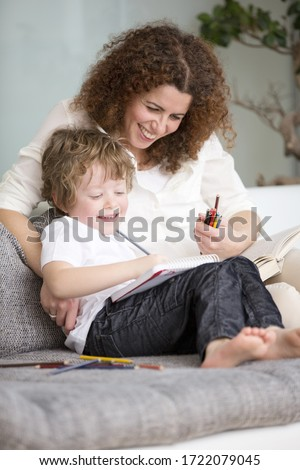 Mother and son drawing in notepad on sofa