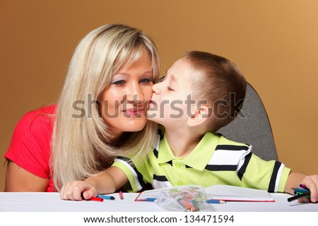 mother and son drawing together, helping with homework, child kissing mom on cheek, orange background