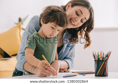 Mother and son drawing with color pencils in living room Foto stock ©