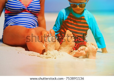 mother and son feet on tropical beach, vacation concept #753891136