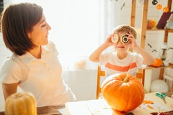 Mother and son have a fun with pumpkins at kitchen at home. Happy Halloween concept