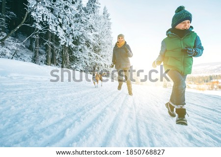 Mother and son having a fun. They running with their beagle dog in snowy forest during dog walk. Mother and son relatives and femily values concept image.
