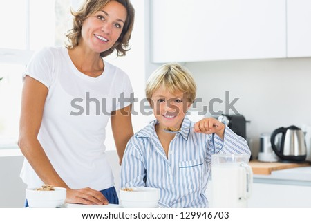 Mother and son having breakfast in kitchen