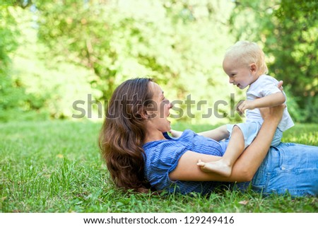 Mother and son having fun on the grass in a park