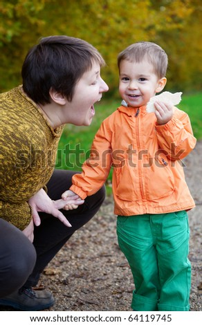 Mother and son having fun together in autumn forest