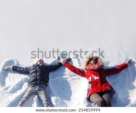 Mother and son having fun together lounging in the snow on a sunny winter day, copy space