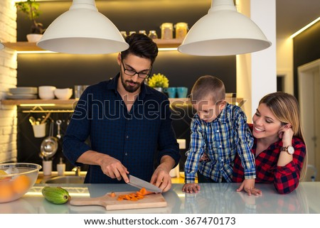 Mother and son helping father to prepare family dinner.