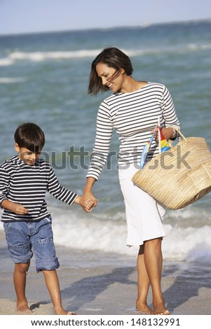 Mother and son holding hands and walking on beach