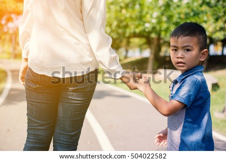 Mother and son holding hands into the sunrise of a summer day in the park #504022582