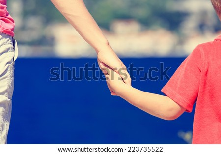 mother and son holding hands on sea vacation