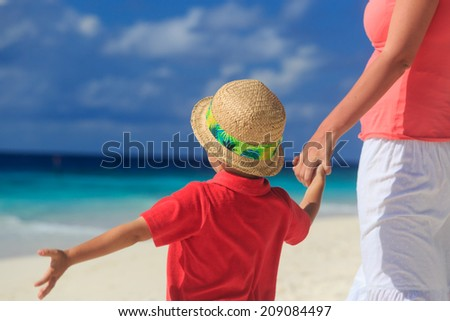 mother and son holding hands on tropical beach vacation