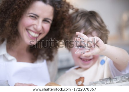Mother and son holding up Christmas tree cookie cutter