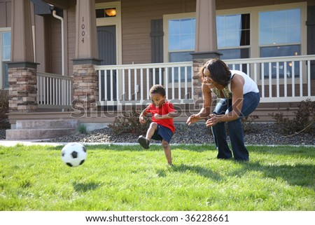 Mother and son in front yard playing with soccer ball