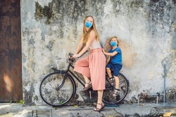 Mother and son in medical mask on a bicycle. Public street art Name Children on a bicycle painted 3D on the wall that's two little Chinese girls riding bicycle in Georgetown, Penang, Malaysia Tourists