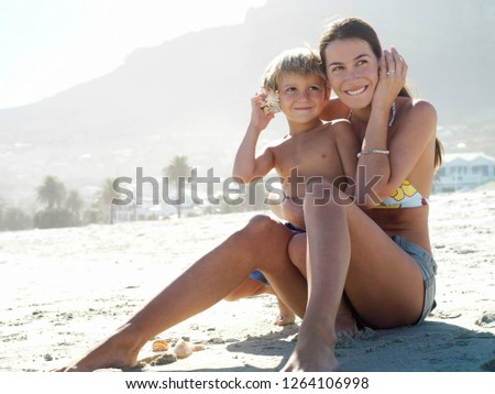 Mother and son in swimwear sitting on sandy beach listening to sea shells on summer vacation