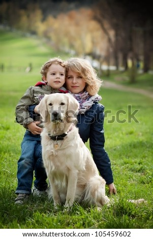 Mother and son in the park along with a golden retriever.