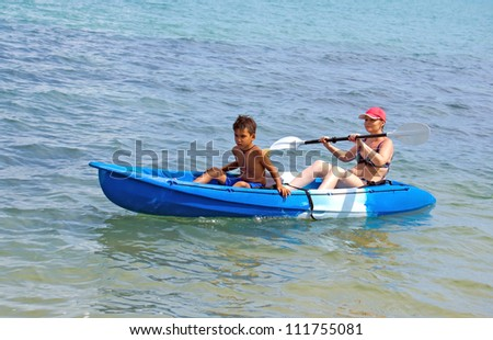 Mother and son kayaking at tropical sea - stock photo