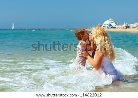 mother and son kiss in sea water on beach