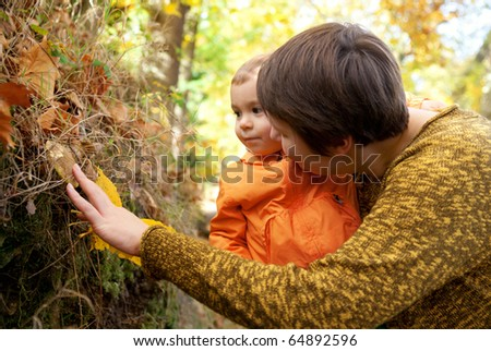 Mother and son looking at mushroom in autumn forest - stock photo