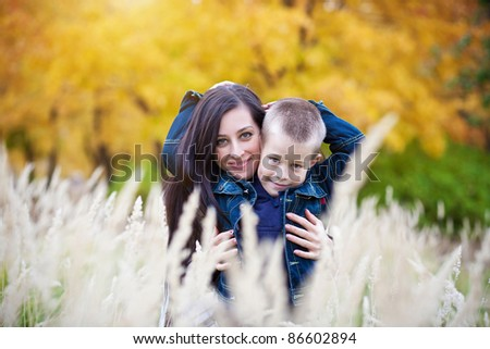 Mother and son on the autumn meadow
