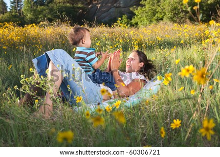 Mother and son playing on a blanket in nature