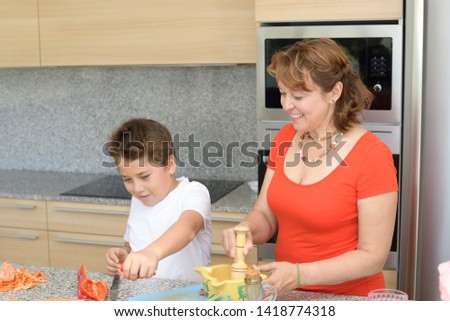 Mother and son preparing lunch in the kitchen and smiling. Child cuts red pepper and put in a bowl. Mom prepares a traditional sauce with a mortar