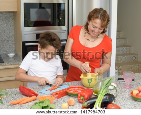 Mother and son preparing lunch in the kitchen and smiling. Child cuts red pepper. Mom prepares a traditional sauce