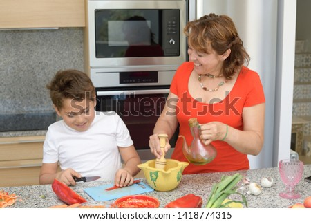 Mother and son preparing lunch in the kitchen and smiling. Child cuts red pepper. Mom prepares a traditional sauce with a mortar an oil