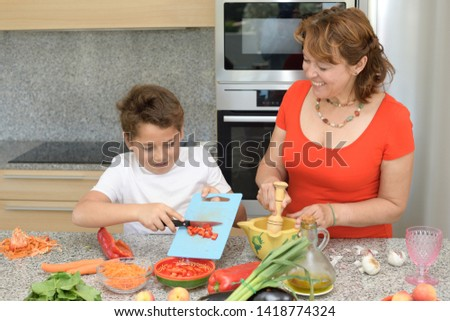 Mother and son preparing lunch in the kitchen and smiling. Child cuts red pepper. Mom prepares a traditional sauce with a mortar
