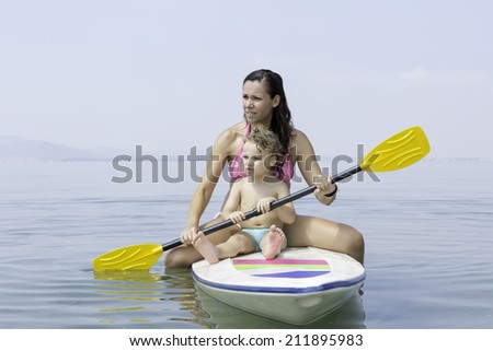 mother and son sitting on a paddle board holding a paddle over a calm sea looking to the infinite
