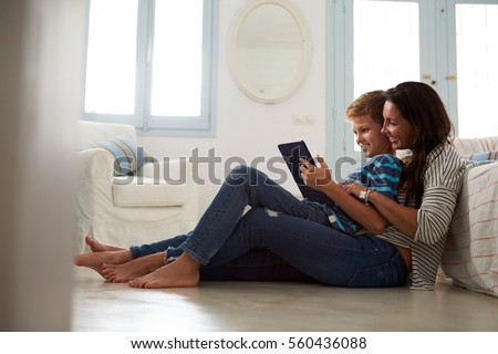 Mother And Son Sitting On Floor Using Digital Tablet