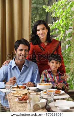 mother and son stand near sitting father at dinner table