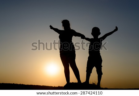 Mother and son standing holding hands on a rock with outspread arms silhouetted by the orange orb of the setting sun at dusk, with copyspace