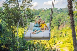 Mother and son swinging in the jungle rainforest of Bali island, Indonesia. Swing in the tropics. Swings - trend of Bali. Traveling with kids concept. What to do with children. Child friendly place