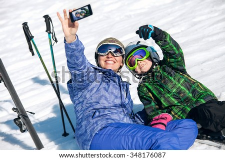 Mother and son take a selfie photo on ski resort