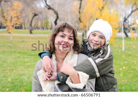 Mother and son together having fun in autumn park