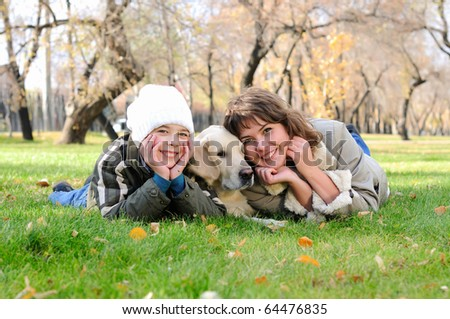Mother and son together having fun in the autumn park playing with a golden retriever.