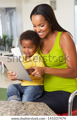 Mother And Son Using Digital Tablet In Kitchen Together